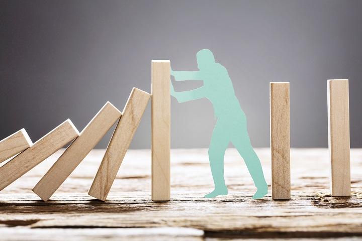 Paperinen hahmo pysäyttämässä kaatuvia dominopalikoita
